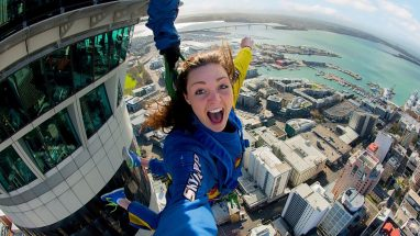 Young women does the SkyJump from the sky tower in Auckland