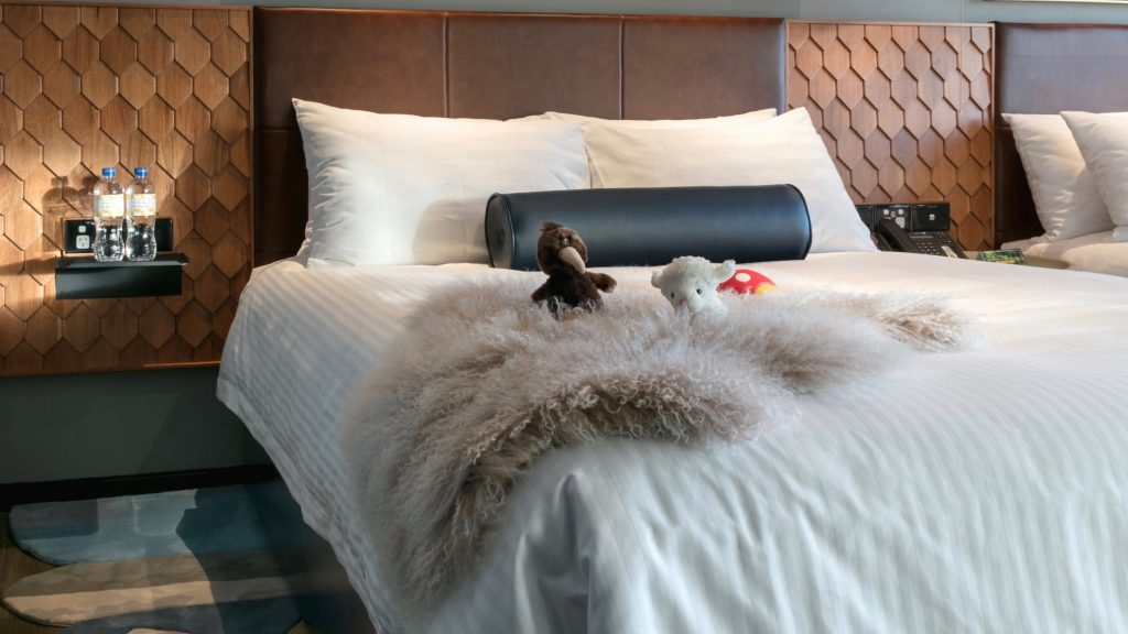 stuffed toys laying on bed in luxurious 5 star hotel room at Naumi Hotel Auckland Airport