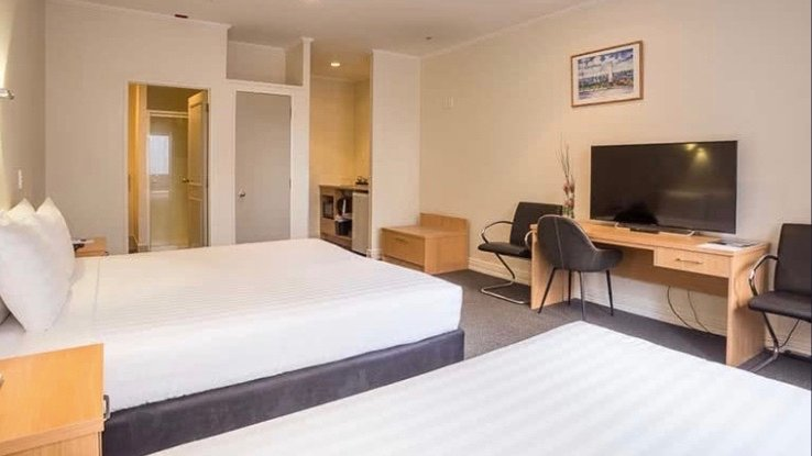 3 star President Hotel Auckland Triple room with cheap furnishings.