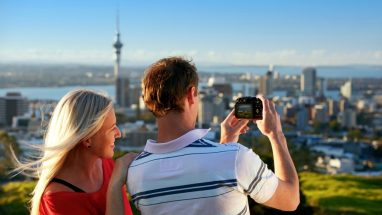 Young couple taking a photo of the view of Auckland city from Mt Eden, Auckland, New Zealand